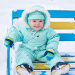 Baby boy sitting on bench in park in winter — Stock Photo #59876135