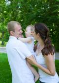 Happy parents with baby boy outdoors — Stock Photo