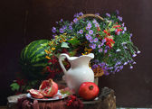 Water-melon, a pomegranate, a white jug and a bouquet in a wattl — Stock Photo