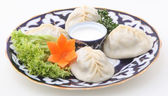 Dumplings submitted with leaves of fresh salad, sour cream and c — Stockfoto