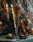 New Year's card with champagne and a candle — Foto de Stock