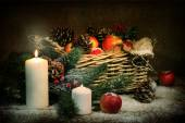 Apples and cones in a basket, candles and fur-tree branches in s — Stock Photo
