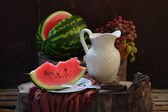 Grapes, a pomegranate, a water-melon and a white jug — Stock Photo
