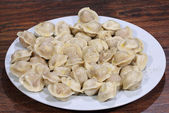Ready pelmeni submitted with the butter, strewed by ground peppe — Stock Photo