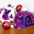 Tinsel, spheres for an ornament of a fur-tree and a gift package — Stock Photo #63368231