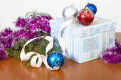 Tinsel, spheres for an ornament of a fur-tree and a gift in beau — Stock Photo