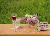 Wine, tea and lilac in a crystal vase — Stock Photo