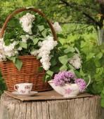 一杯の紅茶と木製のスタブに wattled バスケットのライラック — ストック写真