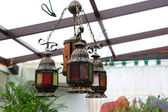 Chandelier from decorative small lamps in a winter garden — Stock Photo