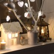 Candles, a decorative small house, fur-tree branches and a small — Stock Photo #65043423