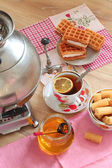 Tea from a samovar, with a lemon, honey, cakes and wafers  — Stock Photo