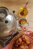 Tea from a samovar, with a lemon, honey and rolls — Stock Photo