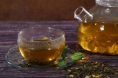 Glass teapot and transparent cup with tea with addition of mint  — Fotografia Stock