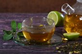 Tea in a glass teapot and a transparent cup with lime and mint o — Photo