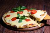 Piece of a pizza with the fused cheese on a wooden shovel — Stock fotografie