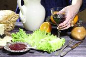 Female hands put on a table a glass with red wine — Stock Photo