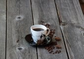 Coffee in a coffee cup in an environment of coffee grains and an — Stock Photo