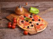 Piece of a pizza and pizza from a salami, a ham and tomatoes on — Stock Photo