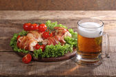 Beer in a transparent mug and chicken beaters in bacon on a wood — Stock Photo
