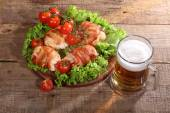Beer in a transparent mug and chicken beaters in bacon submitted — Stock Photo