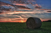 Hay bales on a meadow against beautiful sky with clouds in sunset in hdr photo — Stock Photo