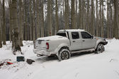 Snow covered car in forest — Stock Photo