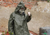 Man with gas mask and green military clothes  explores  small plant  after chemical disaster. — Photo