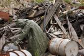 Man with gas mask and green military clothes  explores barrels after chemical disaster. — Photo