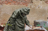 Man with gas mask and green military clothes  explores   dead bird after chemical disaster. — Photo
