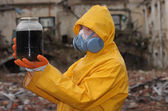 Man with protective  mask and protective  clothes explores danger jar — Photo