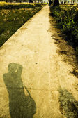 Field road and shadow of man — Stock Photo