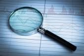 Magnifying glass with financial graph — Stock Photo