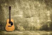 Acoustic guitar against old wall — Stock Photo
