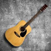 Acoustic guitar on gray wall — Stock Photo