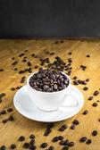 Fincan kahve çekirdekleri masada dolu — Stok fotoğraf