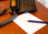 Blank paper on the wooden  desk with the pencil and telephone — Stockfoto
