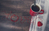 Red clews in shape of heart and cup on wooden back — Stock Photo