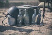 Soldier helmet with ammo box and empty bottles — Stock Photo