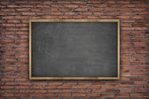 Black blank blackboard with wooden frame on brick wall background — Stock Photo