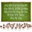 Alphabets concept on blackboard with wooden frame and block letters — Stock Photo #76518117