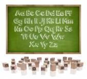 Alphabets concept on blackboard with wooden frame and block letters — Stock Photo
