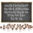 Alphabets concept on blackboard with wooden frame and block letters — Stock Photo #76803445