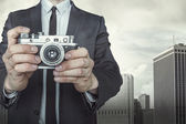 Businessman taking a photo with vintage camera — Stock Photo