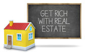 Get rich with real estate on blackboard — Stock Photo