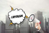 Capitalism text on speech bubble and businessman hand holding megaphone — Stock Photo