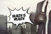 Health is wealth text with businessman wearing boxing gloves — Stock Photo