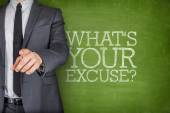 Whats your excuse on blackboard with businessman — Stock Photo