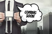 Coming soon text on speech bubble with businessman holding diskette — Stock Photo
