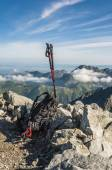 Black and red hiking poles and a backpack — Stock Photo