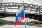 Russian flag above the water on the background of the bridge — Стоковое фото